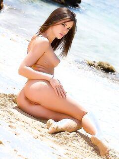 Голая девушка шалит на мокром песке