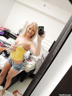 Привлекательная блондинка делает голые селфи перед зеркалом