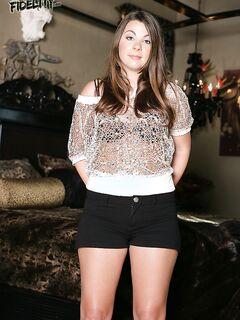 Молодая гимнастка в темных шортиках светит грудь