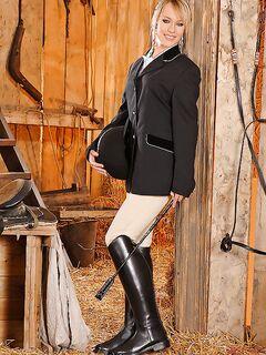 Блондинка в горячей униформе танцует стриптиз в конюшне