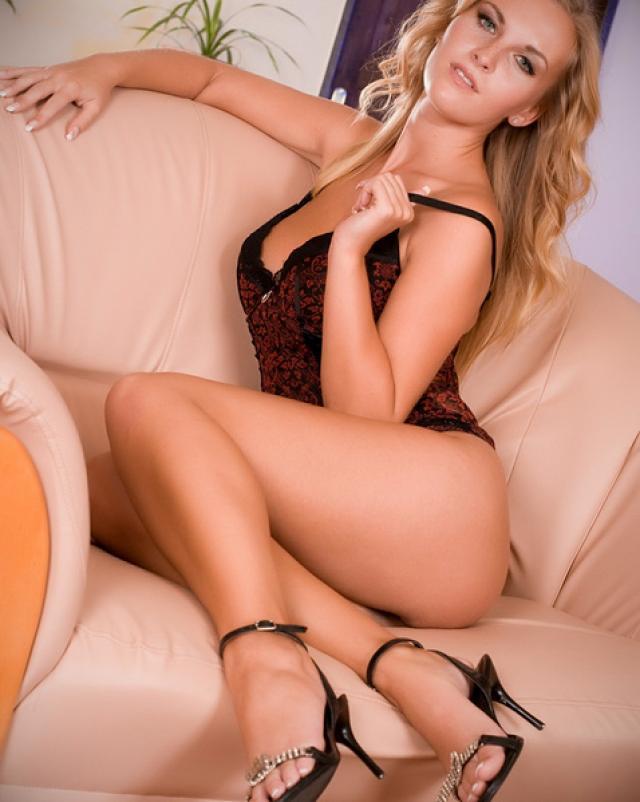 Блондинка с большими натуральными сиськами позирует на диване