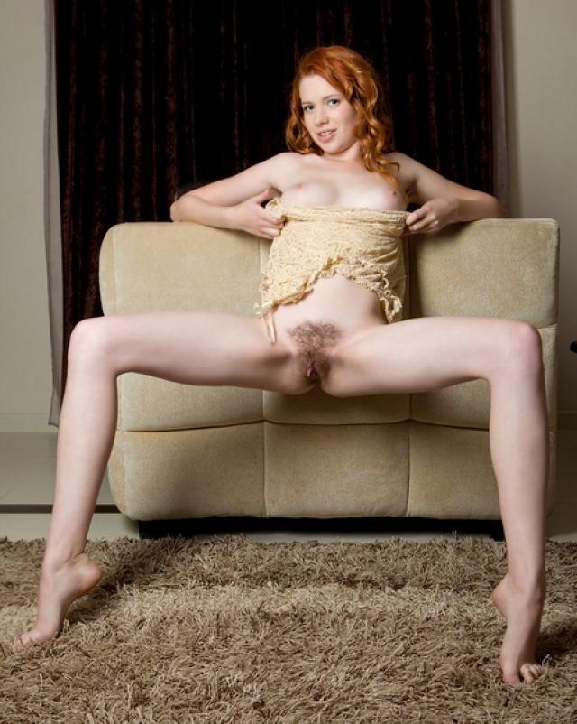 Волосатая рыжая девушка сексуально позирует у дивана