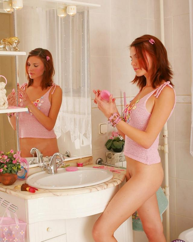 Молоденькая рыжая девушка балуется в ванной на фотокамеру