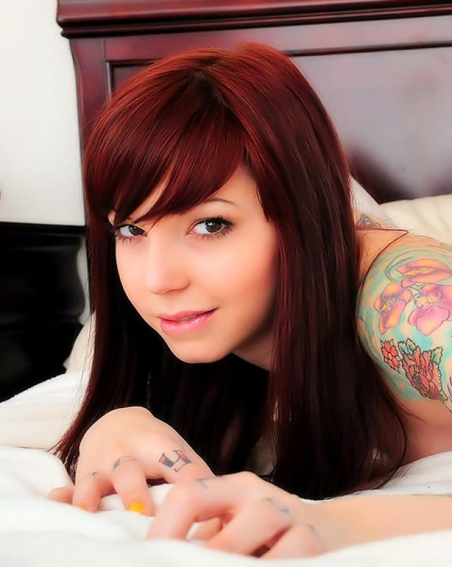 Рыжая девушка с красивой татуировкой шалит в спальне