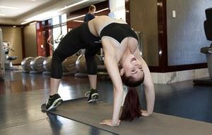 Красивая гимнастка со стройной попкой занимается в спортзале