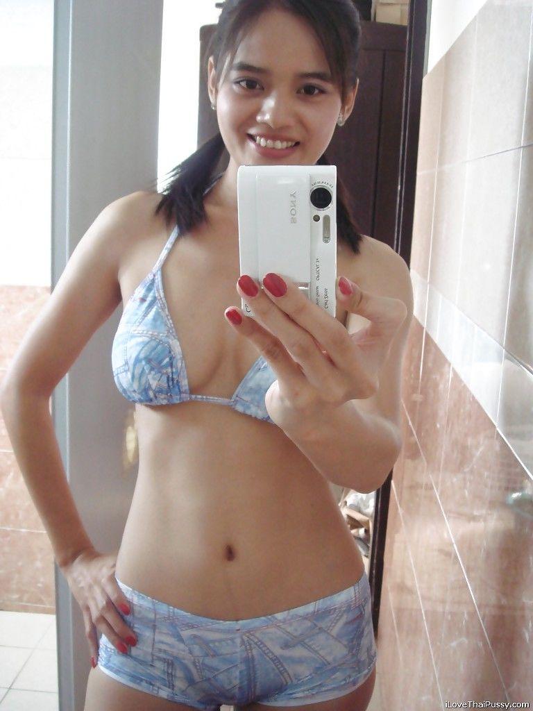 Худенькая азиатка фотографируется обнаженной перед зеркалом