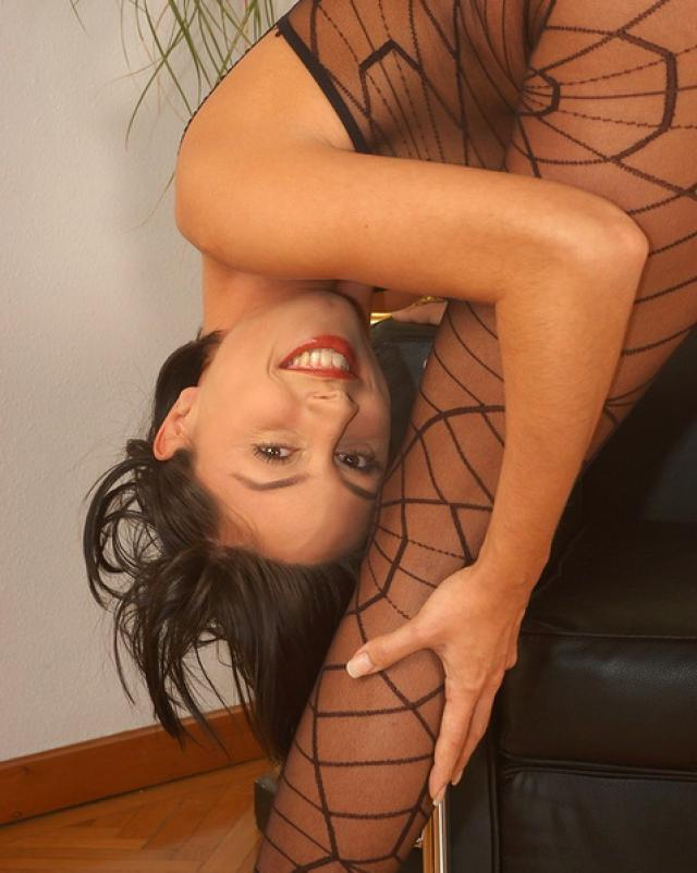 Гибкая девушка позирует в чулочном костюме у кресла