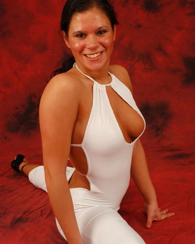 Гибкая девушка в белом платье эротично растягивается