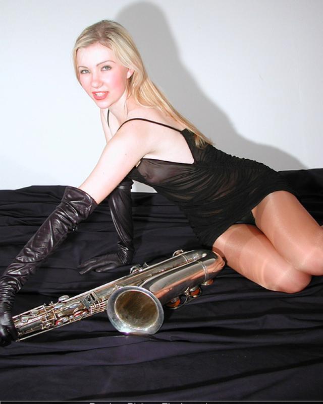 Красивая гимнастка играет на саксофоне