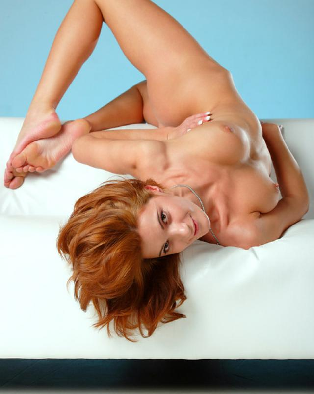 Голая гимнастка позирует на белом диване