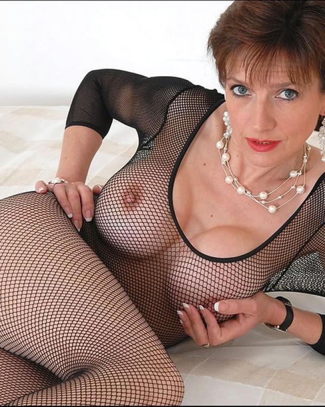 Зрелая леди эротично позирует в фетишных колготках на кровати