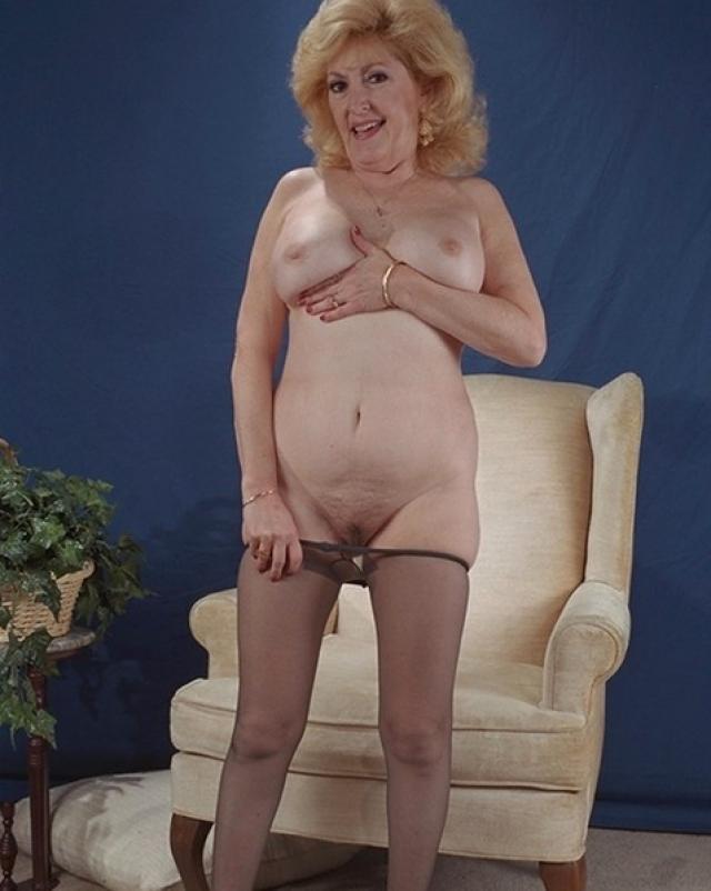 Зрелая дама с крупными сиськами играется с колготками