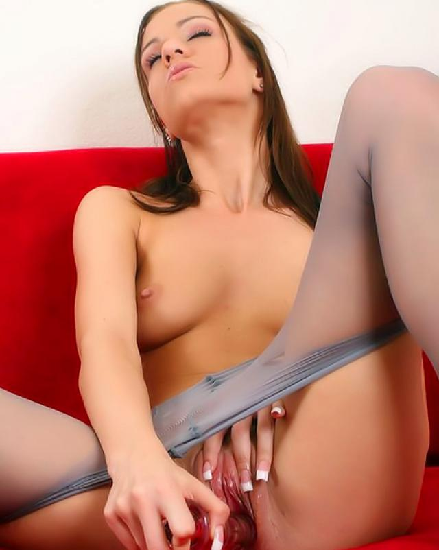 Девушка в серых колготках ублажает себя фаллоимитатором на диване