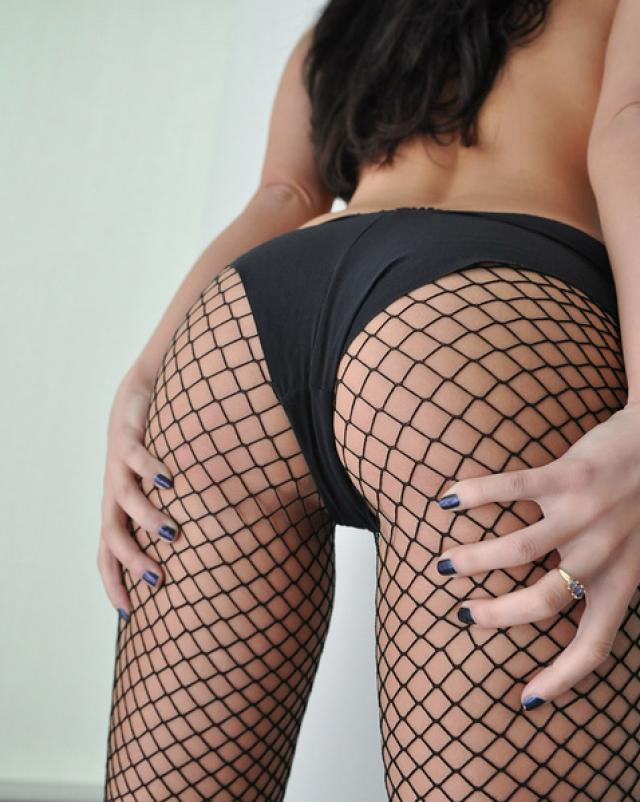 Брюнетка в сексуальных колготках показывает задницу