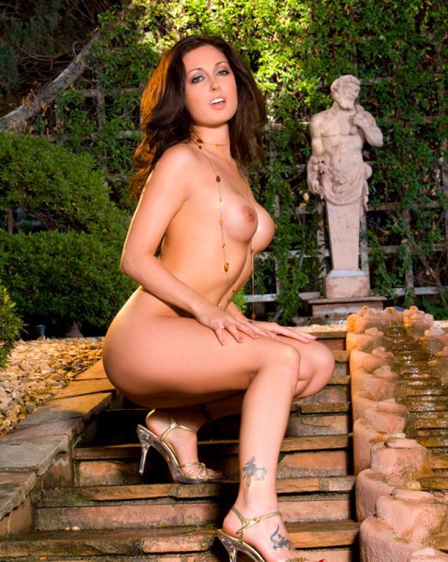 Брюнетка на высоких каблуках раздевается в саду