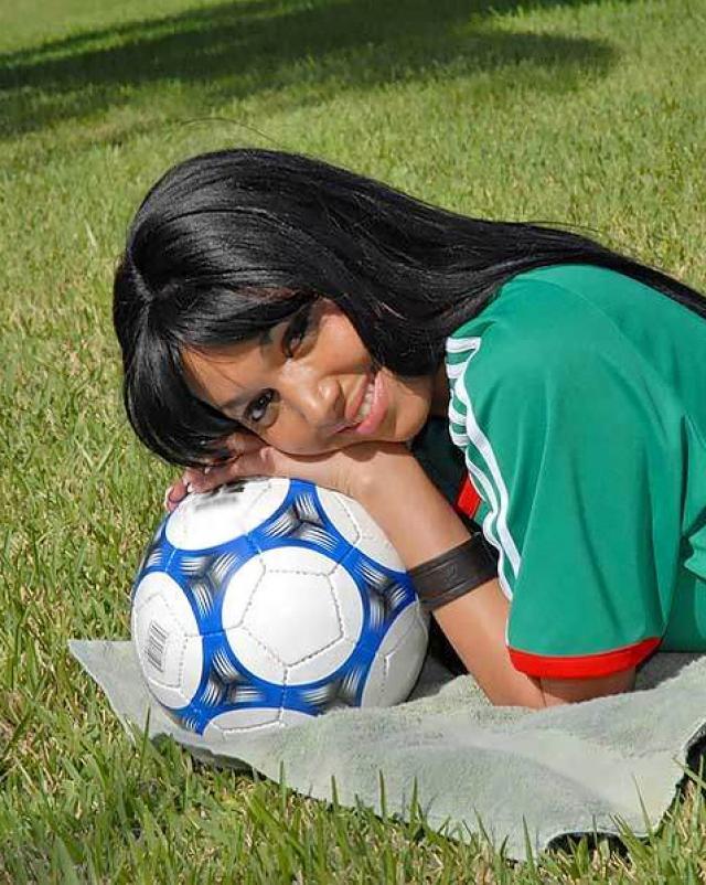 Спортивная девушка шалит на футбольном поле