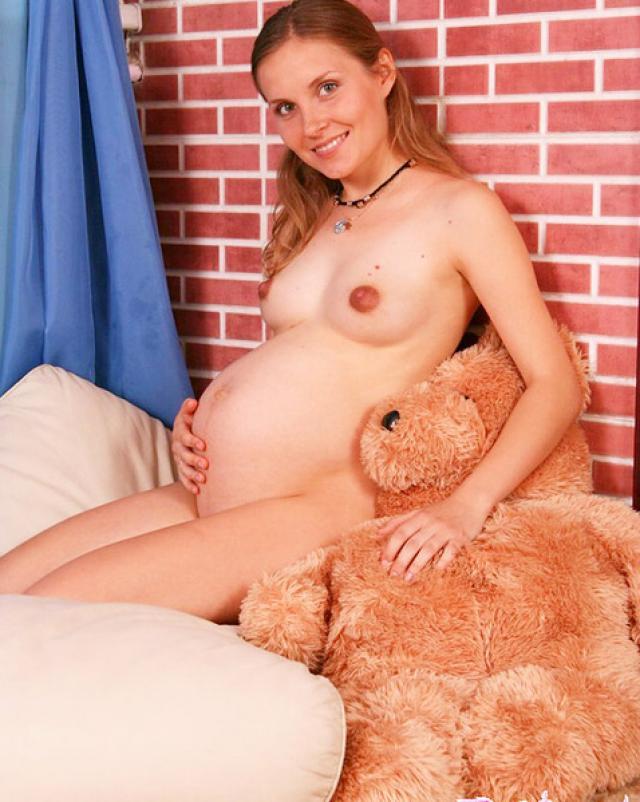 Беременная девушка в нижнем белье эротично раздевается