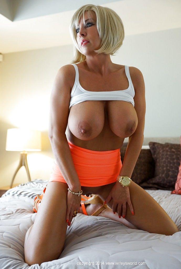 Сисястая жена Sandra Otterson позирует на кровати и показывает вагину