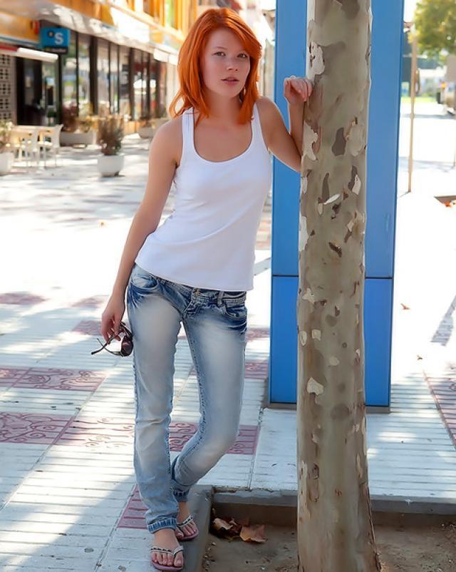 Рыжая студентка в джинсах раздевается в саду