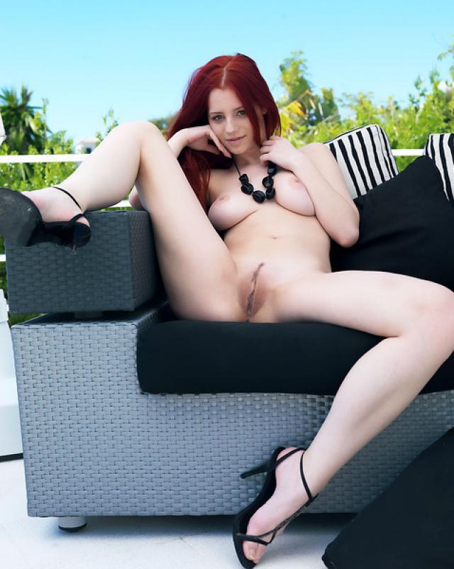 Рыжая красотка сексуально позирует на свежем воздухе
