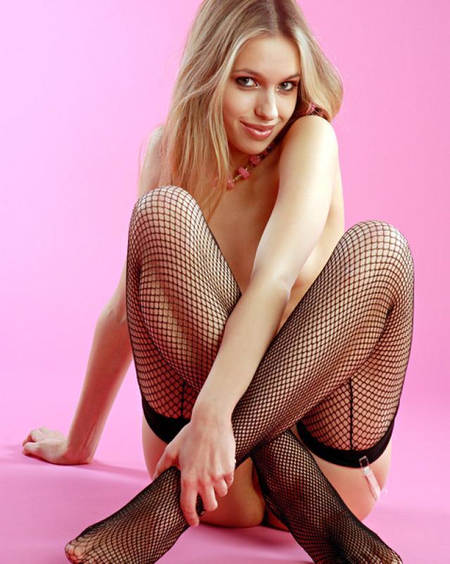 Блондинка с идеальным телом эротично позирует в сетчатых колготках