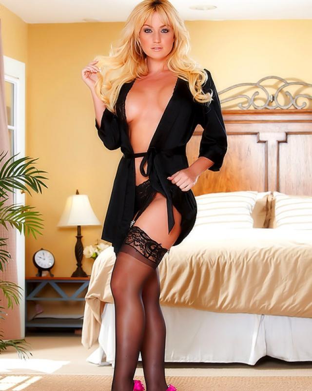 Гламурная блондинка в темных колготках нежно теребит письку на кровати