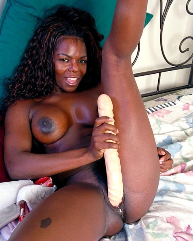 Негритянка теребит письку крупным планом в спальне