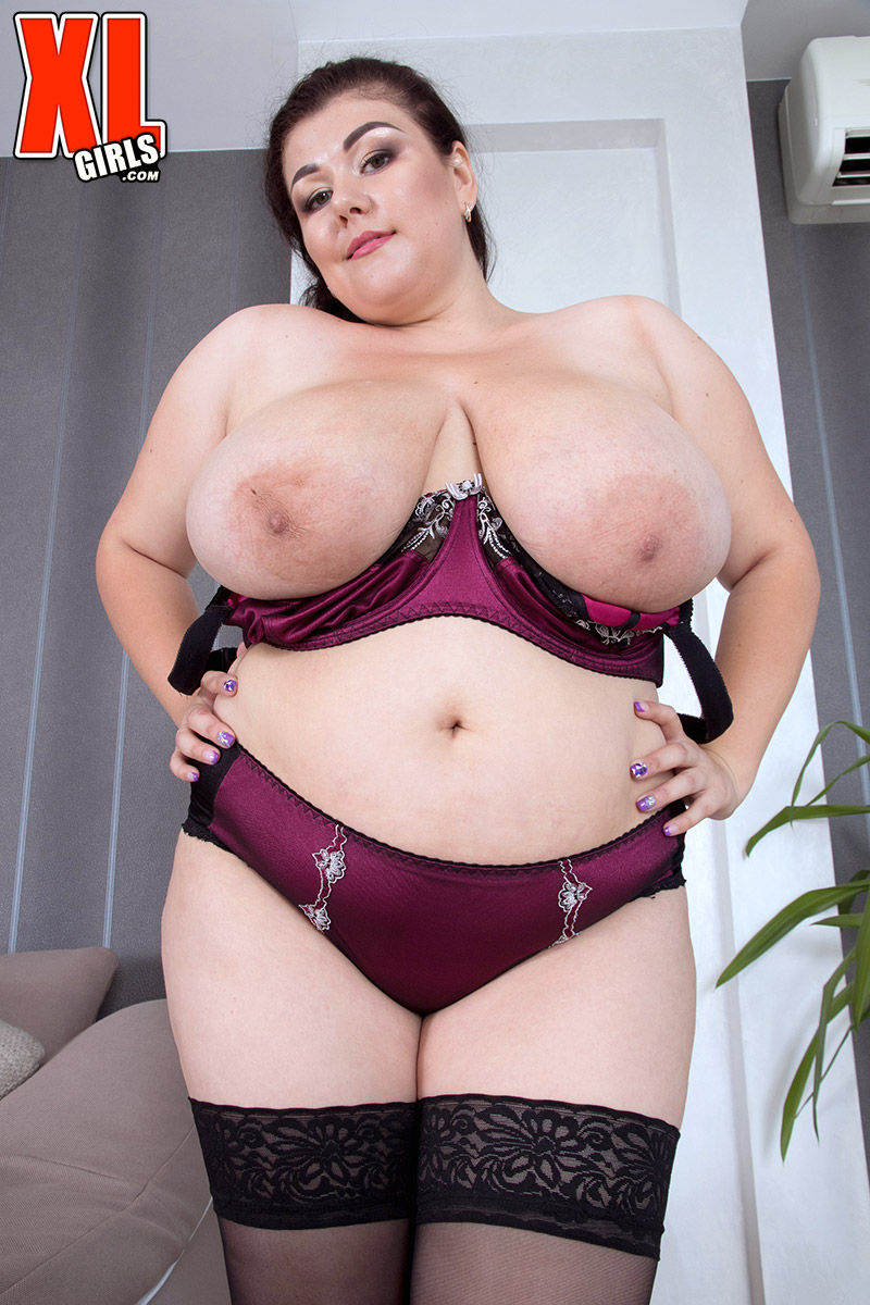 Толстая брюнетка в чулках демонстрирует огромные груди