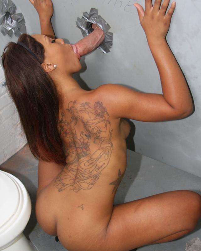 Черная девушка в джинсовых шортах делает минет через дыру в туалете