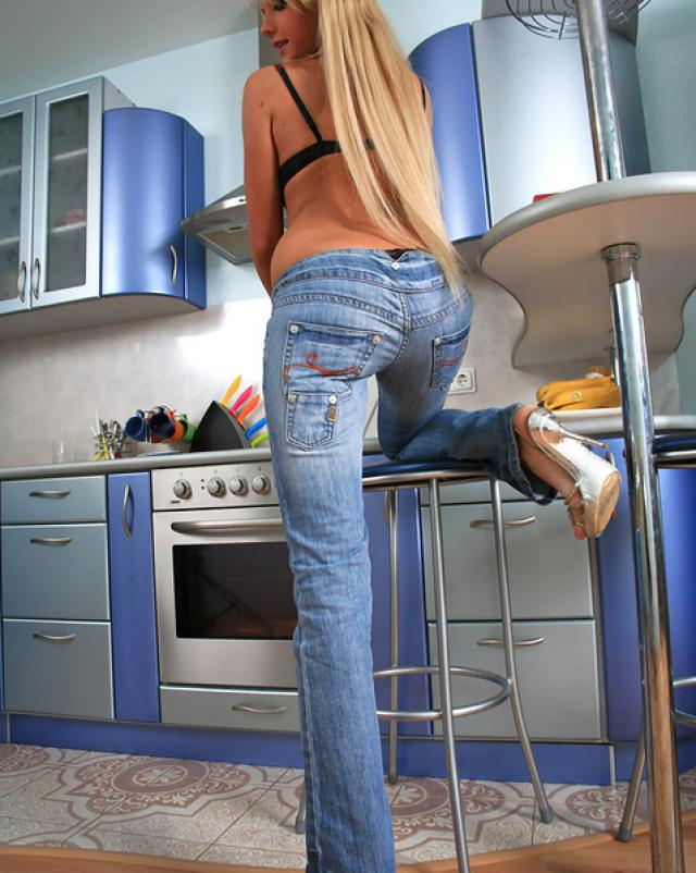 Красотка в джинсах танцует домашний стриптиз на кухне