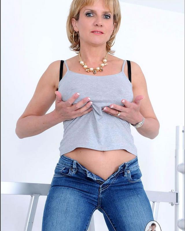 Зрелая женщина в джинсах ласкает свою письку