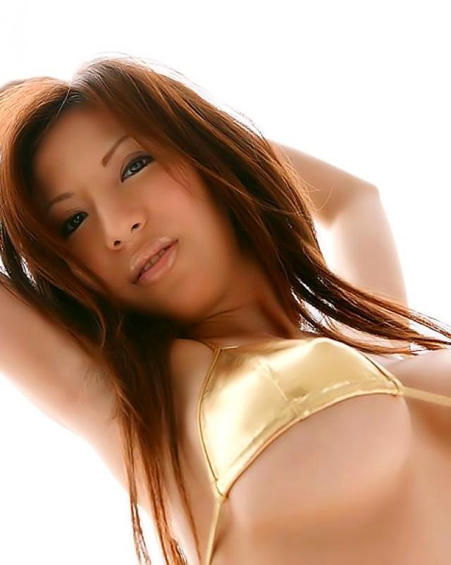 Азиатка в золотистых трусиках хвастает своей большой грудью