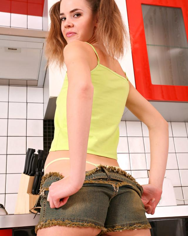 Молоденькая девушка позирует в трусиках на кухне