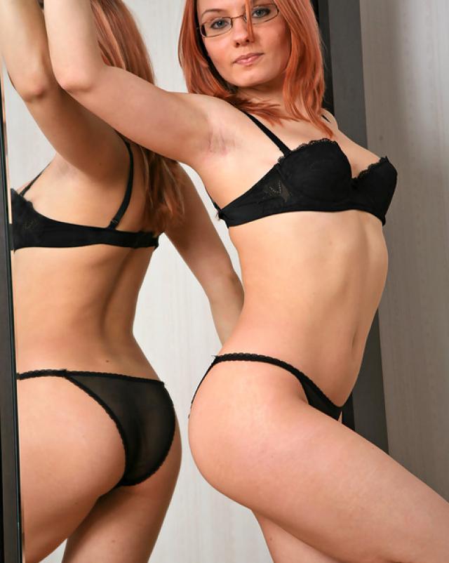 Рыжая девушка любуется в зеркале своей жопой в прозрачных трусах