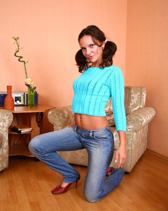 Русская брюнетка с косичками игриво расстегивает джинсы