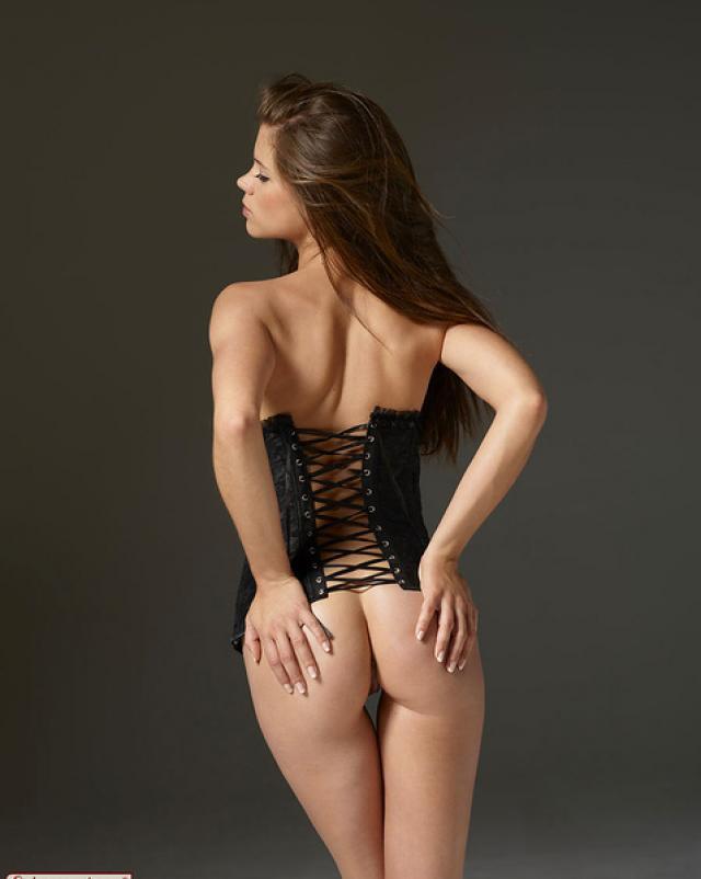 Длинноногая шатенка в корсете манит своим телом