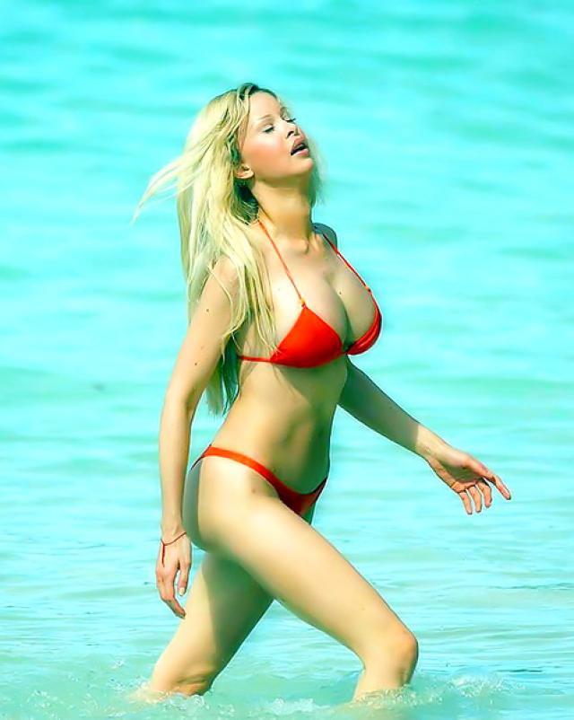 Знаменитая женщина светит большими дойками на пляже