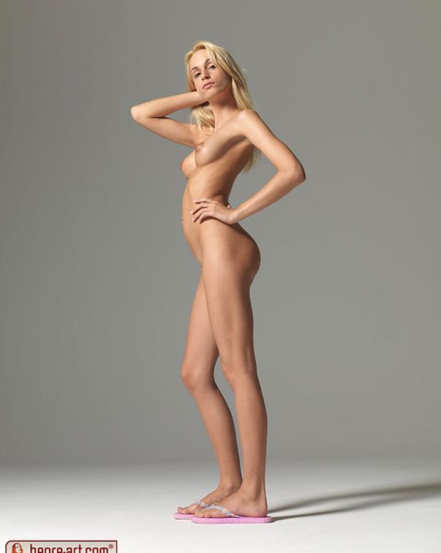 Худая девушка с длинными ногами показывает свое голое тело