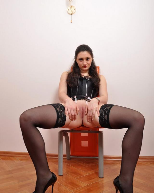 Брюнетка сексуально позирует в черном корсете и чулочках