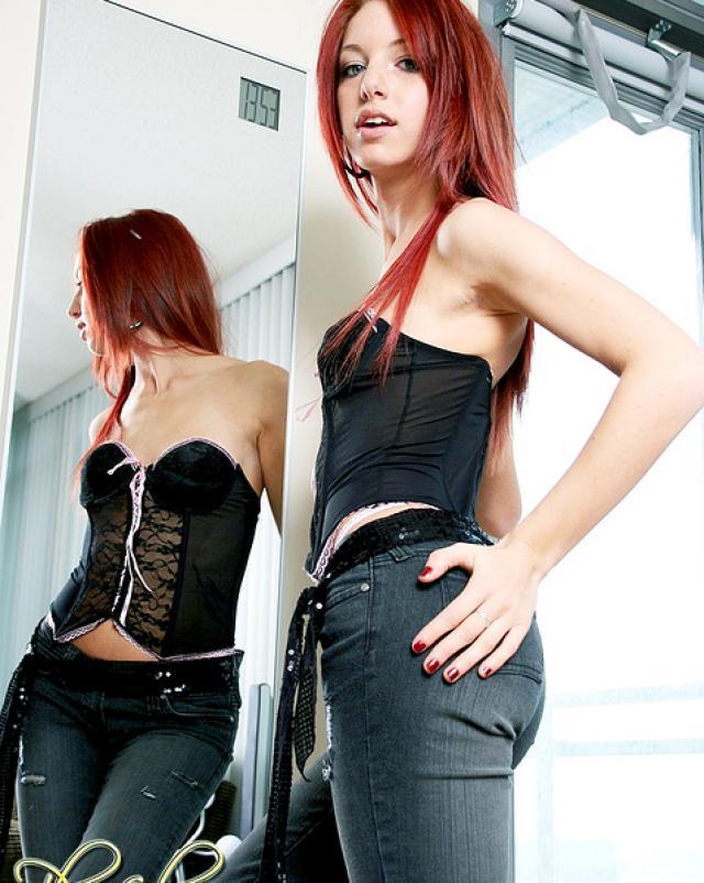 Худая девушка в обтягивающих джинсах шалит у зеркала