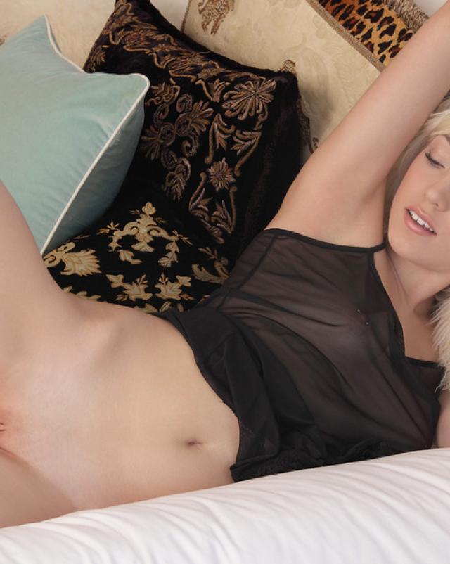 Блондинка в эротичной темной ночнушке на кровати