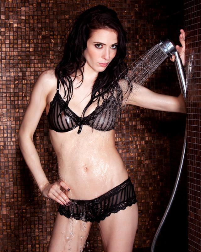 Худая брюнетка в трусиках сексуально принимает душ