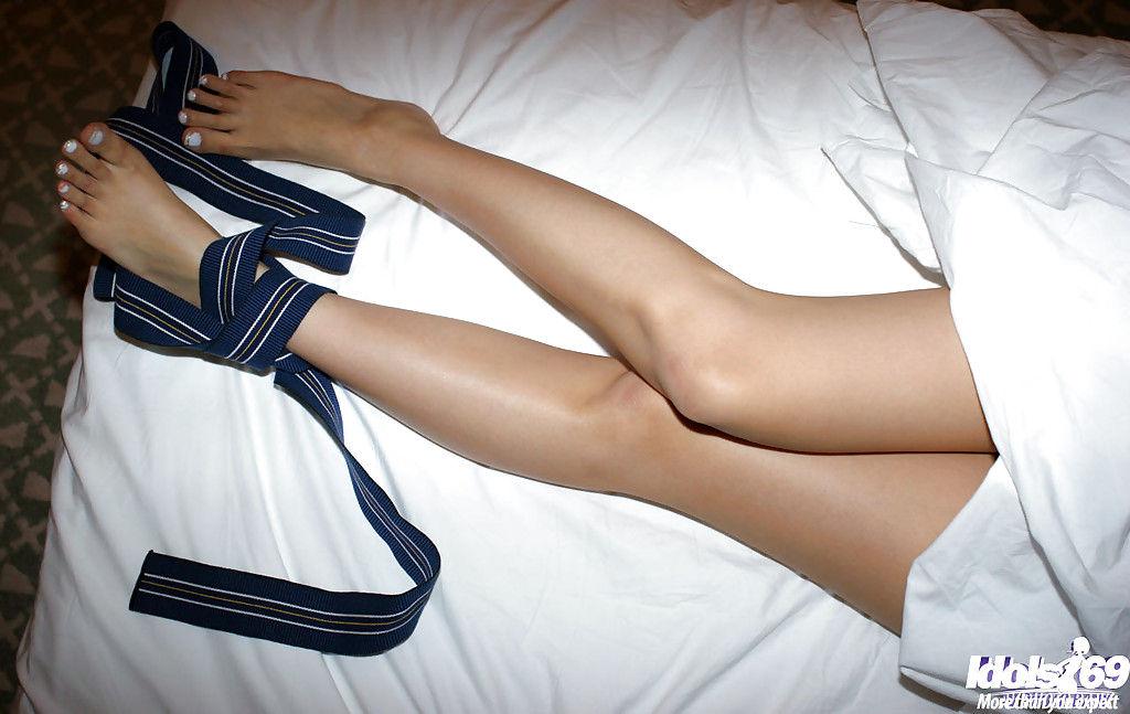 Голая японка трогает себя за волосатую вагину