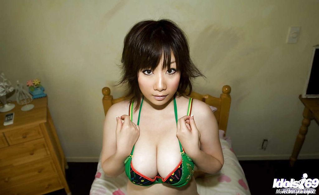 Японская девушка обнажает и гладит свое тело на кровати