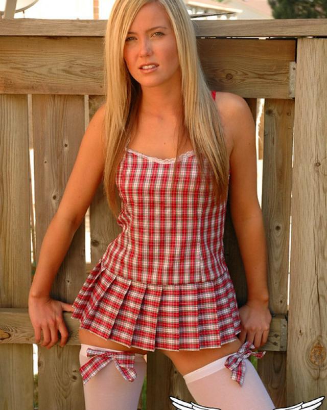 Красивая блондинка раздевается у деревянного забора