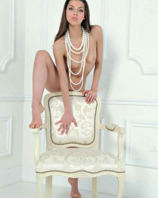 Молодая сексуальная брюнетка в бусах позирует голенькой