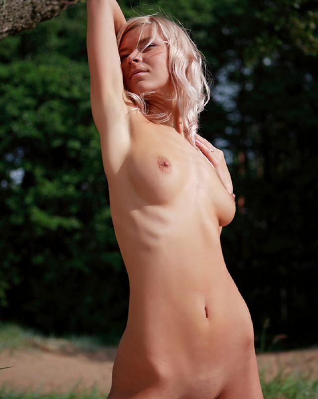 Блондинка с тонкой талией позирует на природе