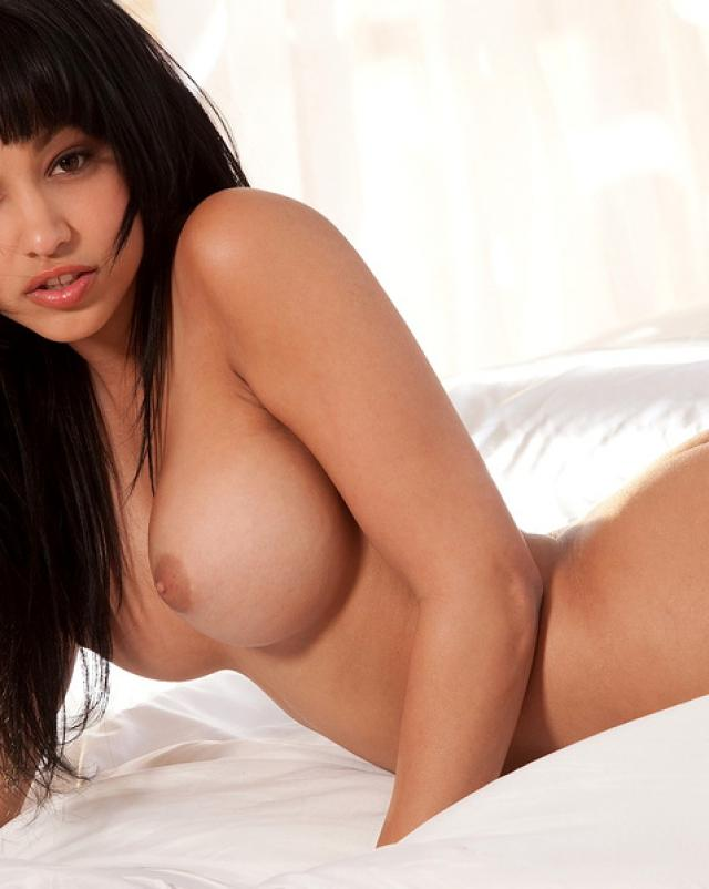 Брюнетка с красивой грудью шалит на кровати